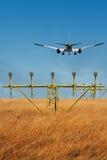 Ein Landungsflugzeug, das über ein Feld fliegt Stockbilder