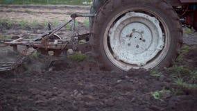 Ein Landwirt auf einem roten Traktor pflügt das Land in seinem kleinen Plan Arbeit für die Landwirtschaft stock video