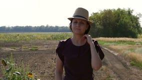Ein Landwirt der jungen Frau in einem Hut geht über das Feld Das Konzept der Landwirtschaft stock video footage