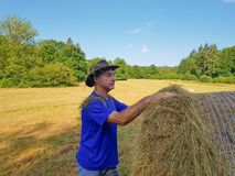 Ein Landwirt in einem Hut steht an einem Stapel frischem Heu lizenzfreie stockfotografie
