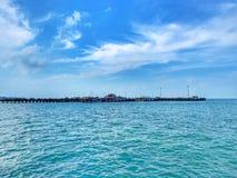 Ein langer Pier zum Ozean zwischen dem blauen Meer und dem blauen Himmel lizenzfreies stockfoto