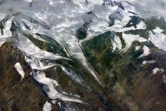 Ein langer weißer Gletscher schiebt unten vom Hochgebirge und von den Schnee-mit einer Kappe bedeckten Spitzen von Spitzen, eine  Lizenzfreie Stockfotos