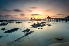 Ein langes Belichtungsbild des goldenen Sonnenaufgangs mit Steinanlegestelle Stockfotografie