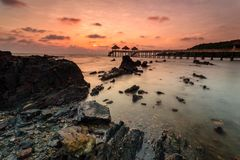 Ein langes Belichtungsbild des goldenen Sonnenaufgangs mit Steinanlegestelle Stockbild