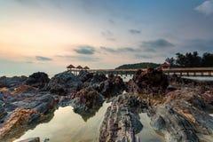 Ein langes Belichtungsbild des goldenen Sonnenaufgangs mit Steinanlegestelle Lizenzfreie Stockfotos