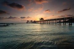 Ein langes Belichtungsbild des goldenen Sonnenaufgangs mit Steinanlegestelle Stockfotos