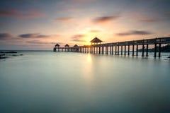 Ein langes Belichtungsbild des goldenen Sonnenaufgangs mit Steinanlegestelle Stockfoto