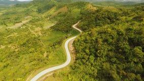 Ein langes und eine kurvenreiche Straße überschreiten durch grüne Hügel Busuanga-Insel Coron Schattenbild des kauernden Geschäfts stock video footage