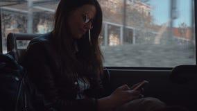 Ein langhaariges Mädchen in der Sonnenbrille, die in einem beweglichen Bus sitzt stock footage
