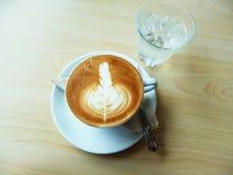 Ein Latte-oder Cappuccino Kaffee mit Lattekunst auf dem hölzernen Schreibtisch Stockbild