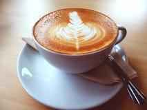 Ein Latte-oder Cappuccino Kaffee mit Lattekunst auf dem hölzernen Schreibtisch Lizenzfreies Stockfoto