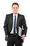 Ein lächelnder Geschäftsmann, der einen Laptop anhält Lizenzfreies Stockfoto