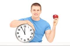 Ein lächelnder Kerl, der eine Wanduhr und einen roten Apfel auf einer Tabelle hält Lizenzfreies Stockfoto