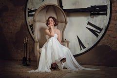Ein lächelndes Mädchen in einem Hochzeitskleid im merkwürdigen Stuhl Die Braut in einem Stuhl auf dem Hintergrund von Uhren und v Stockfotografie