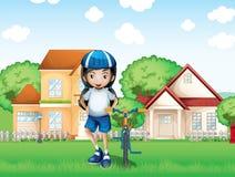 Ein lächelndes Mädchen und ihr Fahrrad nahe den großen Häusern Stockbild