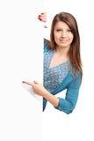 Ein lächelndes schönes Mädchen, das auf ein weißes Panel zeigt Stockfotografie