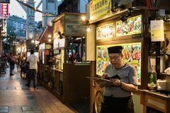 Ein Lebensmittelverkäufer studiert seinen Handy Chinatown-` s an der Lebensmittelstraße, während er auf die Glättungsmenge wartet lizenzfreie stockfotos