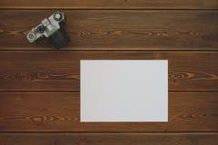 Ein Leerbeleg und eine Weinlesekamera auf einem dunklen Holztisch lizenzfreies stockbild