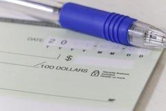 Ein leerer persönlicher Scheck mit einem Stift Lizenzfreies Stockfoto