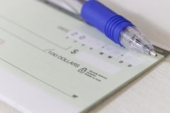 Ein leerer persönlicher Scheck mit einem Stift Stockfoto