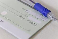 Ein leerer persönlicher Scheck mit einem Stift Stockfotos