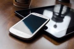 Ein leeres Geschäft Smartphone, das auf Tablet mit Kaffee sich lehnt Stockfoto