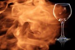 Ein leeres Glas Rotwein im Feuer flammt Stockfotos