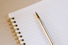 Ein leeres quadratisches Notizbuch mit einem Stift Lizenzfreies Stockbild