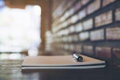 Ein leeres weißes Notizbuch und ein Silber färben Stift auf Holztisch Lizenzfreie Stockbilder