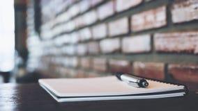 Ein leeres weißes Notizbuch und ein Silber färben Stift auf Holztisch mit Backsteinmauer Stockfoto