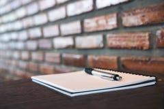 Ein leeres weißes Notizbuch und ein Silber färben Stift auf Holztisch mit Backsteinmauer Lizenzfreie Stockfotos