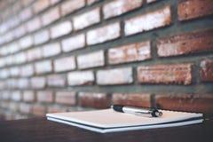 Ein leeres weißes Notizbuch und ein Silber färben Stift auf Holztisch mit Backsteinmauer Stockfotografie