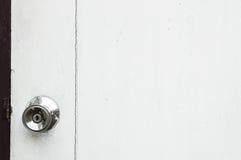 Ein Legierungsmetalltürknauf auf einer weißen Holztür Lizenzfreie Stockbilder