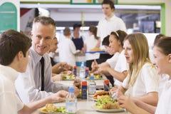 Ein Lehrer, der das Mittagessen mit seinen Kursteilnehmern isst Stockfotografie