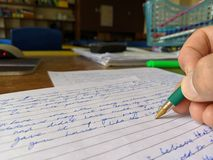 Ein Lehrer, der in der Hand ein Pr?fungspapier an einem Schreibtisch mit gr?nem Stift markiert lizenzfreie stockfotos