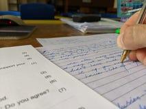 Ein Lehrer, der ein Pr?fungspapier an einem Schreibtisch markiert stockfoto