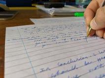 Ein Lehrer, der ein Pr?fungspapier an einem Schreibtisch mit gr?nem Stift markiert stockbild