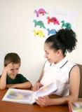 Ein Lehrer liest ein Buch mit ihrem Vorschulkursteilnehmer Lizenzfreies Stockfoto