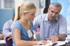 Ein Lehrer weist ein Schulmädchen an lizenzfreie stockfotos