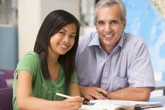 Ein Lehrer weist ein Schulmädchen an Lizenzfreies Stockfoto