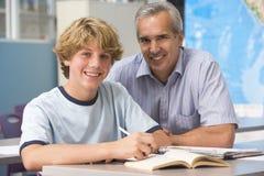 Ein Lehrer weist einen Schüler an Stockbild
