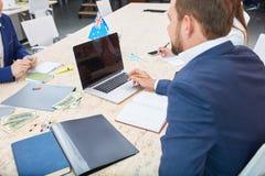 Ein Leiter am Funktionstisch vermischt mit dem Büroangestelltsitzen Innerlich in einem Büro Lizenzfreie Stockfotos