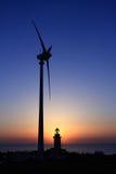 Ein Leuchtturm, eine Windturbine und ein Sonnenuntergang Lizenzfreie Stockfotografie