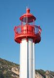 Ein Leuchtturm gegen Hintergrund des Hügels und des blauen Himmels Stockbilder