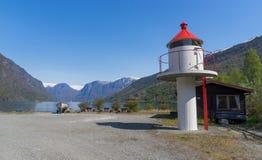 Ein Leuchtturm mit kleinem Boot auf der Küste von Fjord in Flam lizenzfreies stockbild