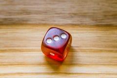 Ein lichtdurchlässiges Rot sechs versah mit Seiten, Würfel auf einem hölzernen Hintergrund spielend Stockfotografie