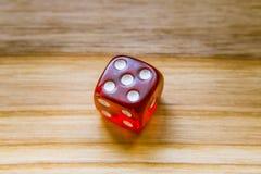 Ein lichtdurchlässiges Rot sechs versah mit Seiten, Würfel auf einem hölzernen Hintergrund spielend Lizenzfreies Stockfoto