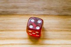 Ein lichtdurchlässiges Rot sechs versah mit Seiten, Würfel auf einem hölzernen Hintergrund spielend Lizenzfreies Stockbild
