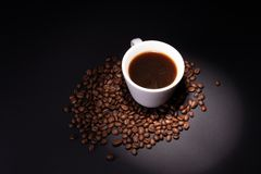 Ein Lichtstrahl wird an einer Tasse Kaffee-Stellung in einem Stapel von Kaffeebohnen verwiesen lizenzfreies stockfoto