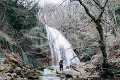 Ein Lieben, stilvolles, junges Paar in der Liebe auf dem Hintergrund eines Wasserfalls stockfotos
